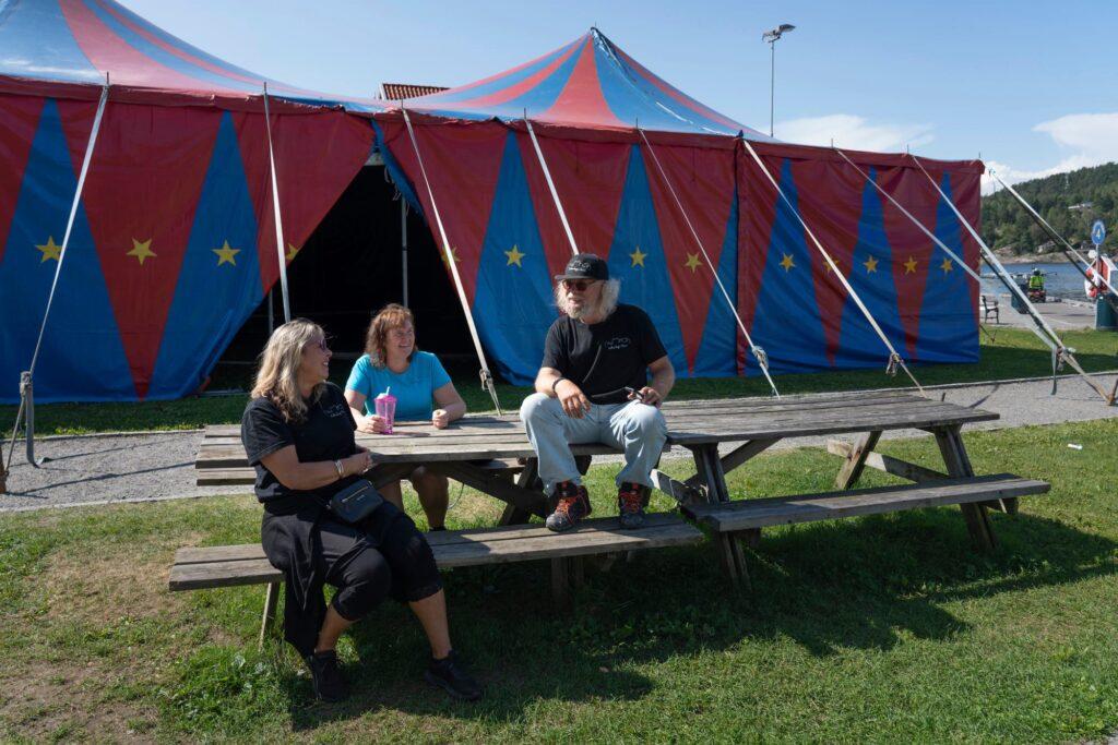 To damer og en mann sitter ved piknikbord foran et sirkustelt. Foto.