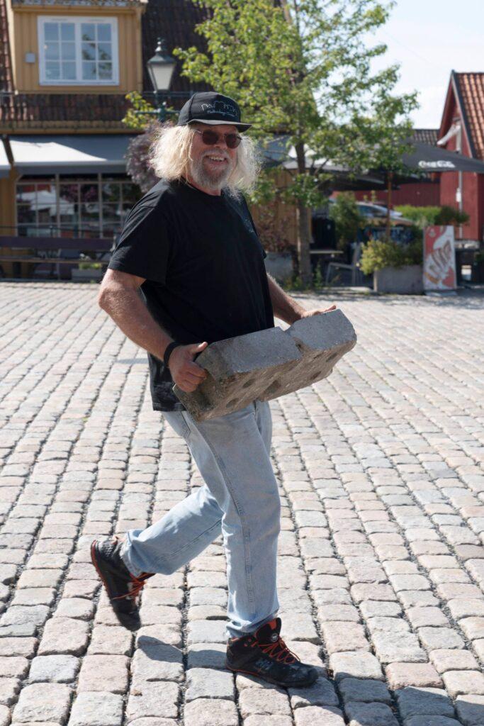 En mann bærer et sementblokk. Foto.