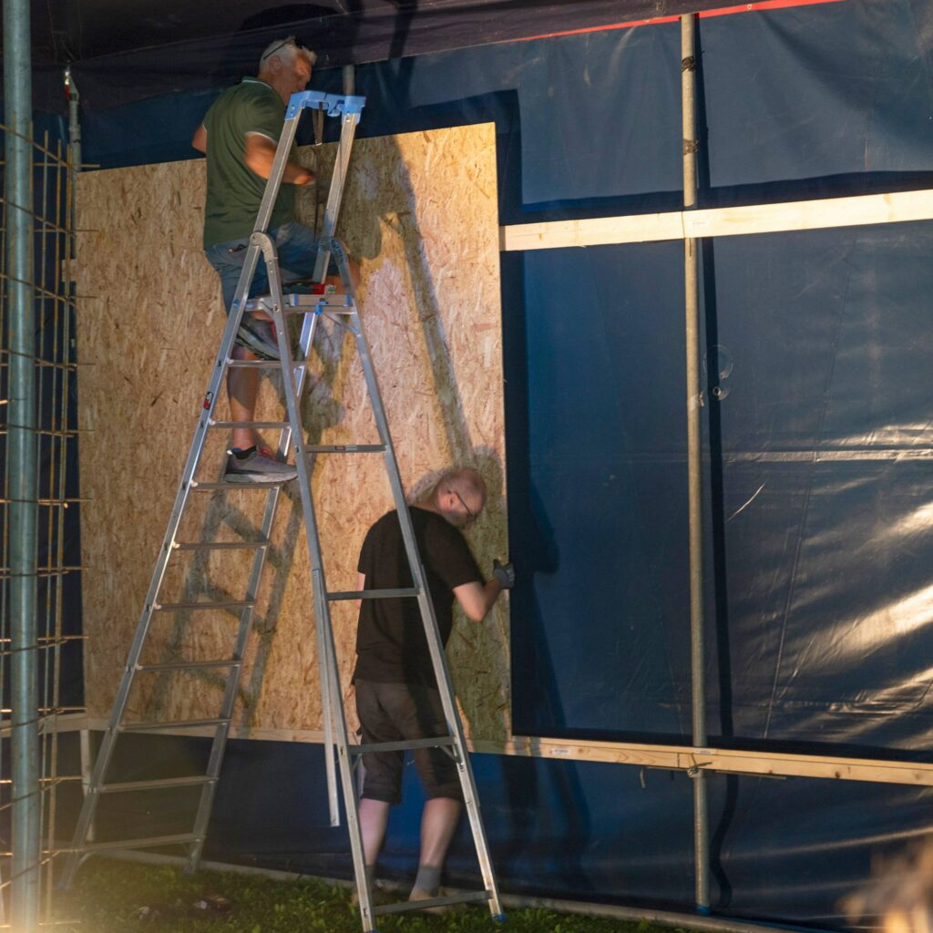 To menn arbeider med å sette opp vegger i et sirkustelt. Foto.